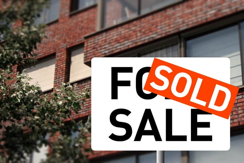 A sold sign and a house on the background