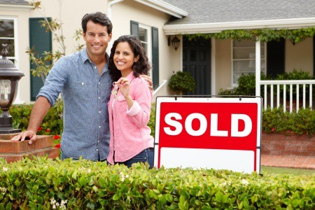 couple with sold sign