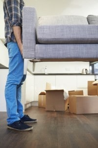 person lifting couch moving boxes