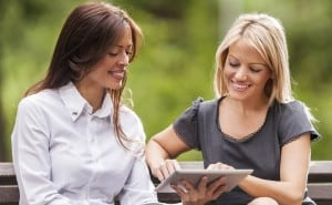 Businesswomen using touchpad outdoors.