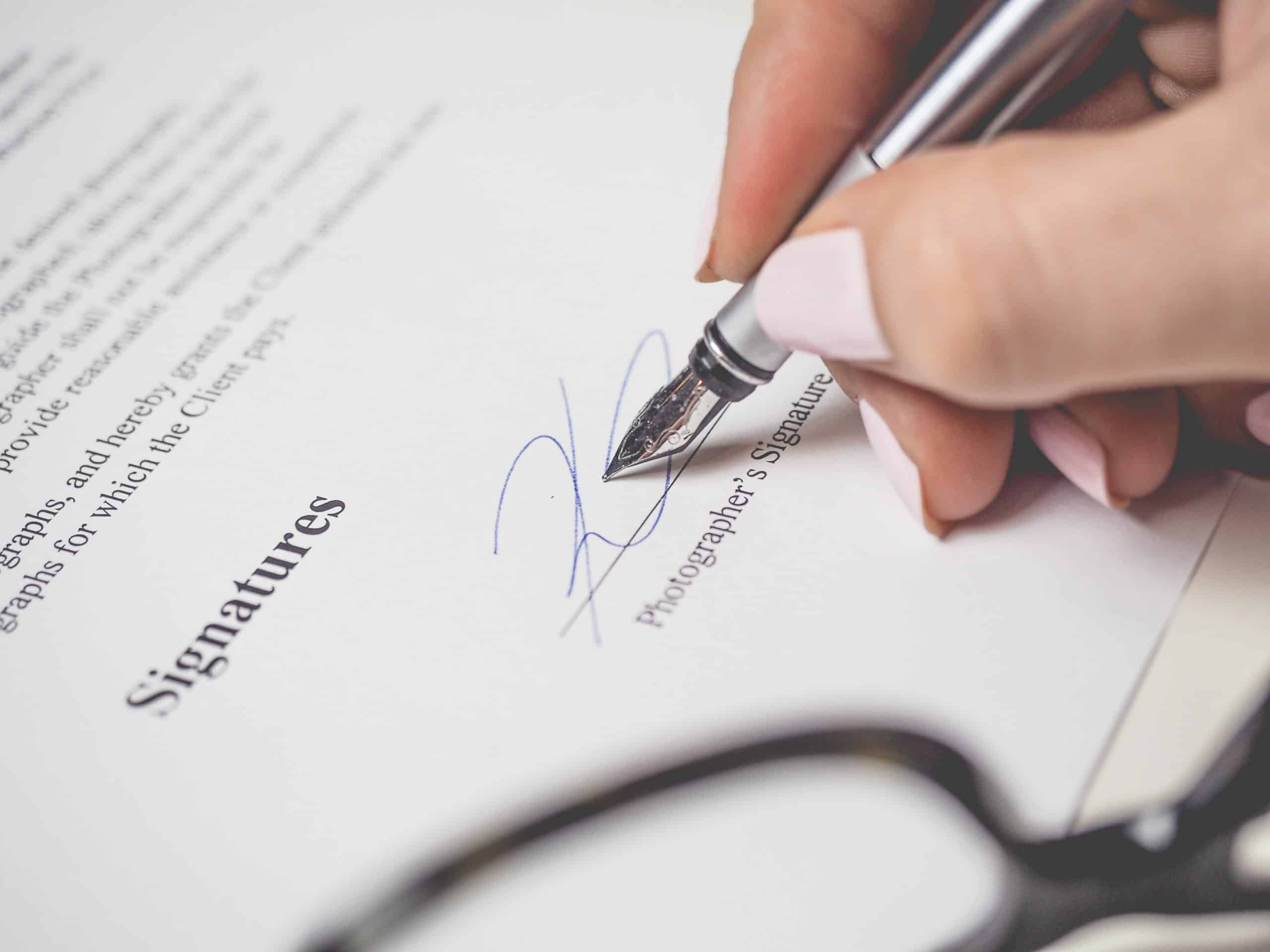 person holding pen, signing document, lease, contracts